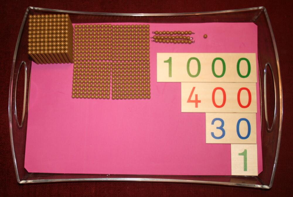 Esercizi coi cartelli dei numeri e le perle dorate Montessori